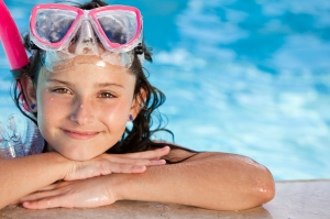 This is an image of a young girl propped on the edge of a swimming pool and smiling. She is resting her chin on her hands and wearing pink goggles and snorkel gear. The blue pool water is seen in the background.